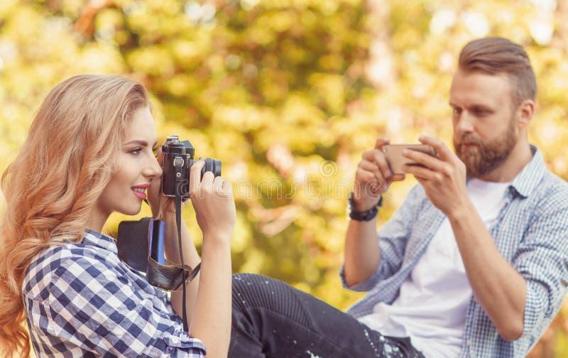 Mann und Frau, die Fotos mit einer Kamera und einem Smartphone im Herbstpark machen stockfoto