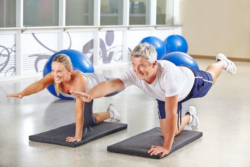 Mann und Frau, die Gymnastik in der Eignungsmitte tun stockfotografie