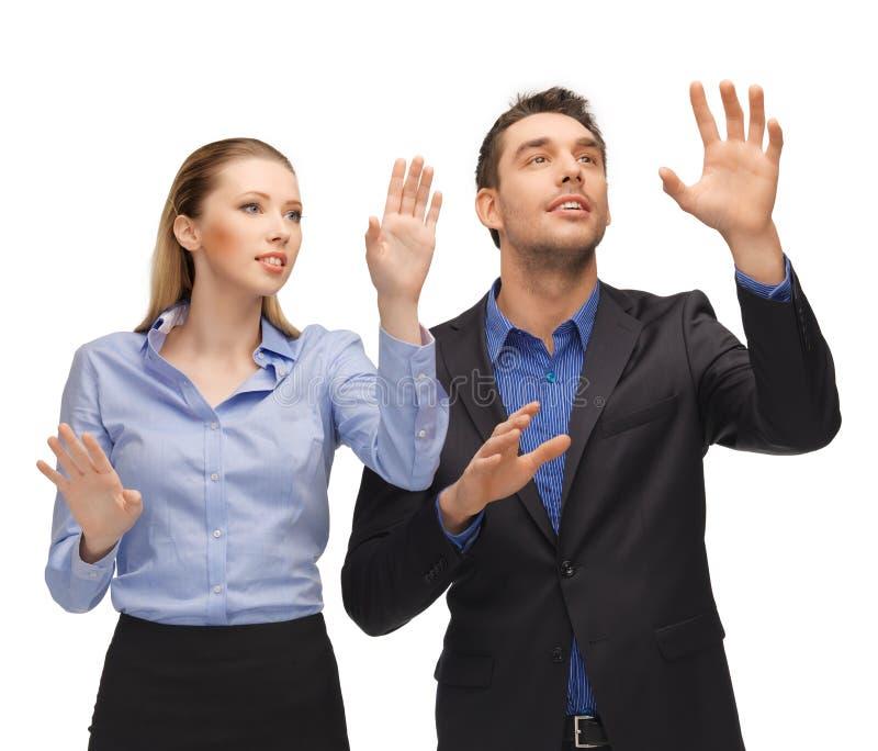 Mann und Frau, die mit etwas eingebildet arbeitet stockfotografie