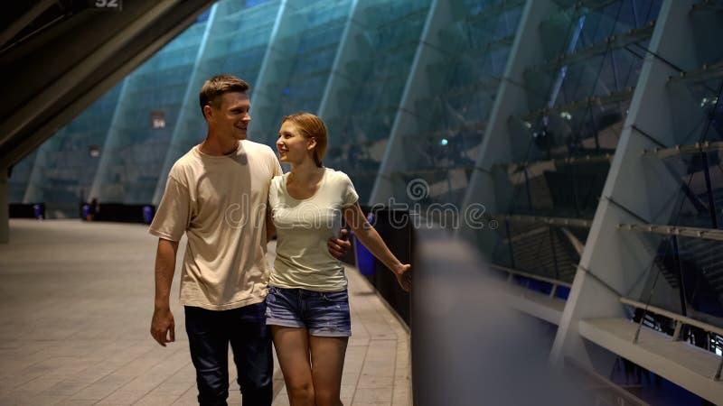 Mann und Frau, die nahe Stadion, WarteFußballspiel, Sportfreunde gehen stockfotografie