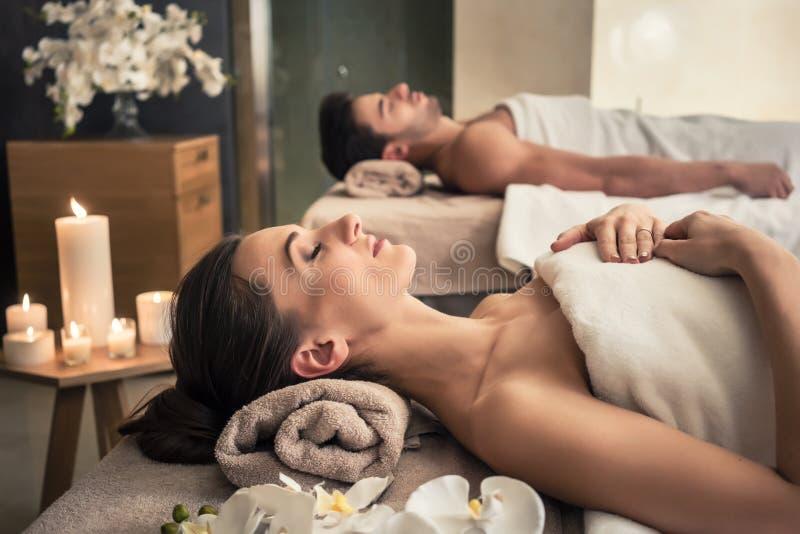 Mann und Frau, die sich auf Massagebetten an asiatischem Wellness cente hinlegen stockfotografie