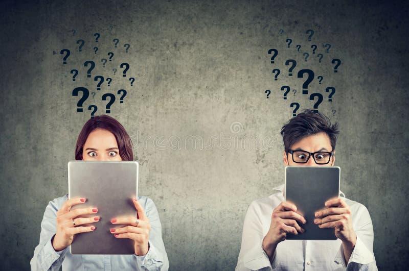 Mann und Frau, die Tabletten hält und mit vielen Fragen verwechselt schaut lizenzfreie stockfotografie