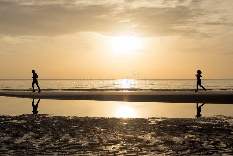 Mann und Frau, die zusammen auf dem Strand im Sonnenuntergang - Sonnenaufgang laufen stockfotos