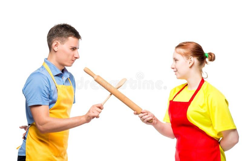 Mann und Frau in einem Schutzblech mit Küchengeräten kämpfend auf einem Weiß stockbild