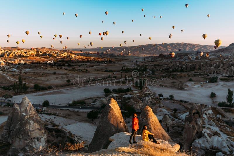 Mann und Frau grüßen die Dämmerung unter Ballonen Paare in der Liebe unter Ballonen Reisende in den Bergen von Cappadocia, die Tü stockfotos
