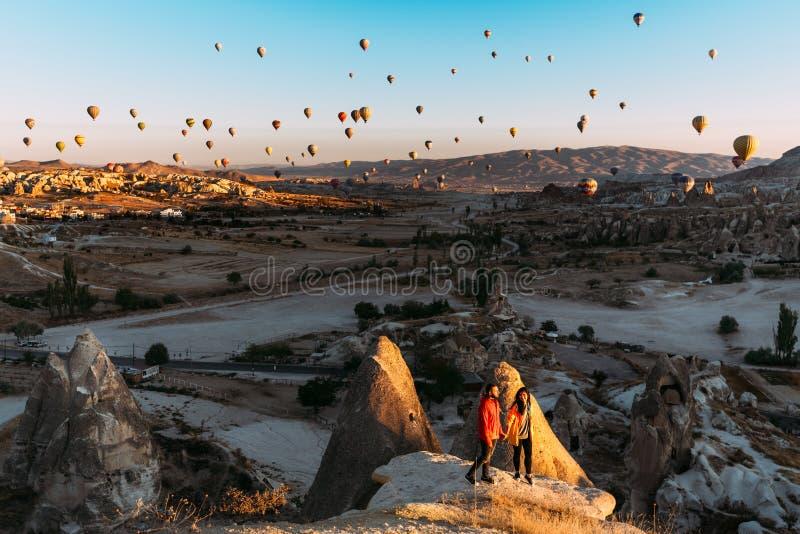 Mann und Frau gr??en die D?mmerung unter Ballonen Paare in der Liebe unter Ballonen Reisende in den Bergen von Cappadocia, die T? lizenzfreies stockfoto