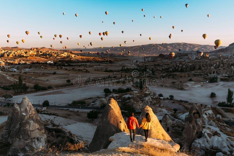Mann und Frau gr??en die D?mmerung unter Ballonen Paare in der Liebe unter Ballonen Reisende in den Bergen von Cappadocia, die T? lizenzfreie stockfotografie