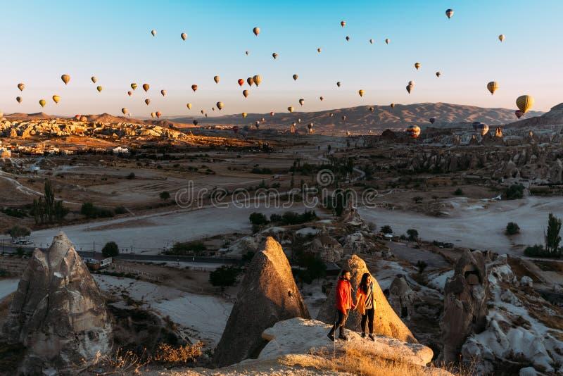 Mann und Frau gr??en die D?mmerung unter Ballonen Paare in der Liebe unter Ballonen Reisende in den Bergen von Cappadocia, die T? stockfotos