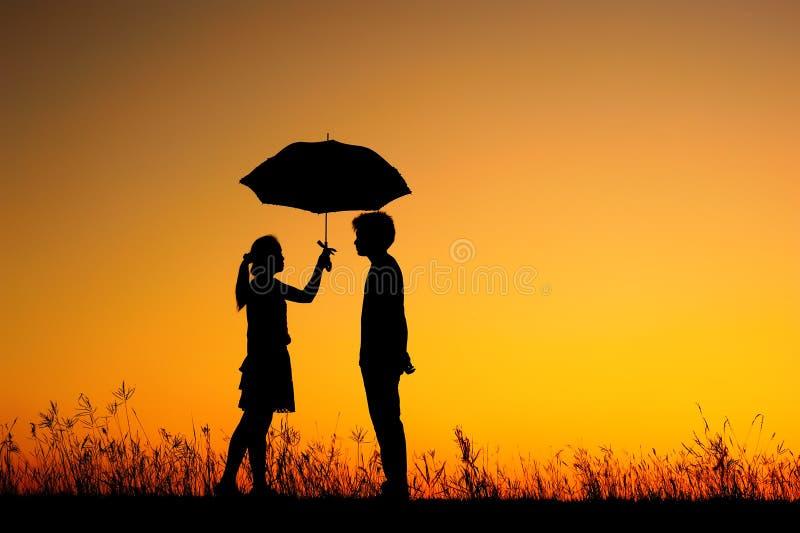 Mann und Frau halten Regenschirm im Abendsonnenuntergang an stockbilder