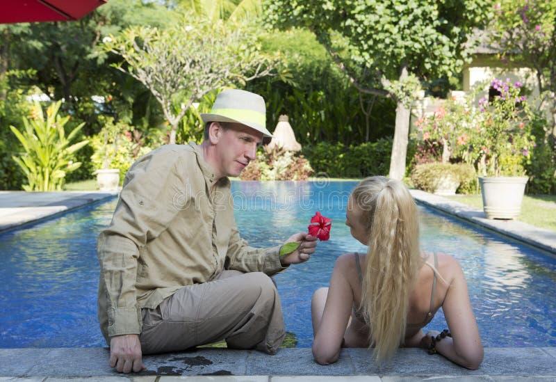 Mann und Frau, liebevolles Paar, am Pool in einem Garten mit tropischen Bäumen Mann gibt der Frau eine Blume stockbild