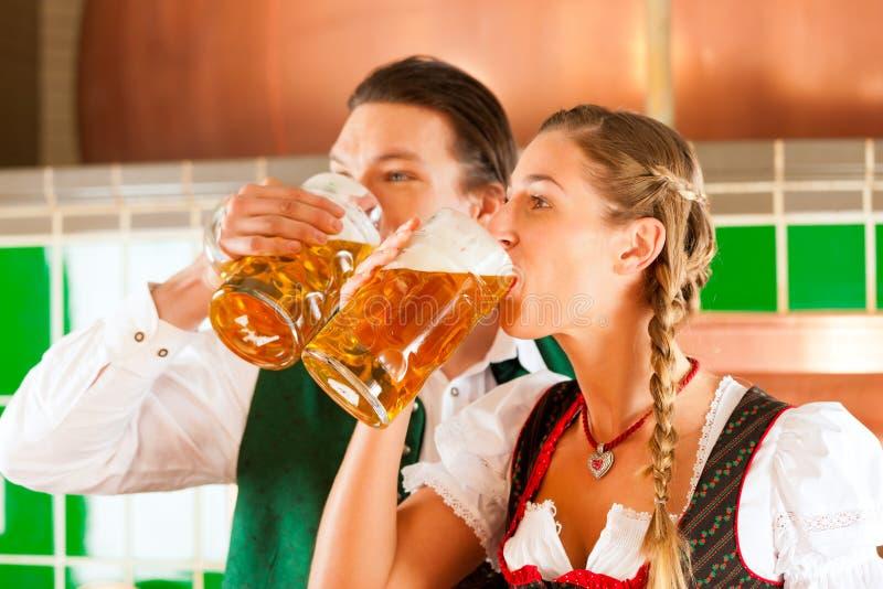 Mann und Frau mit Bierglas in der Brauerei lizenzfreie stockbilder
