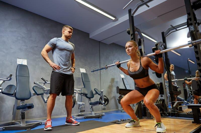 Mann und Frau mit dem barl, das Muskeln in der Turnhalle biegt stockfoto