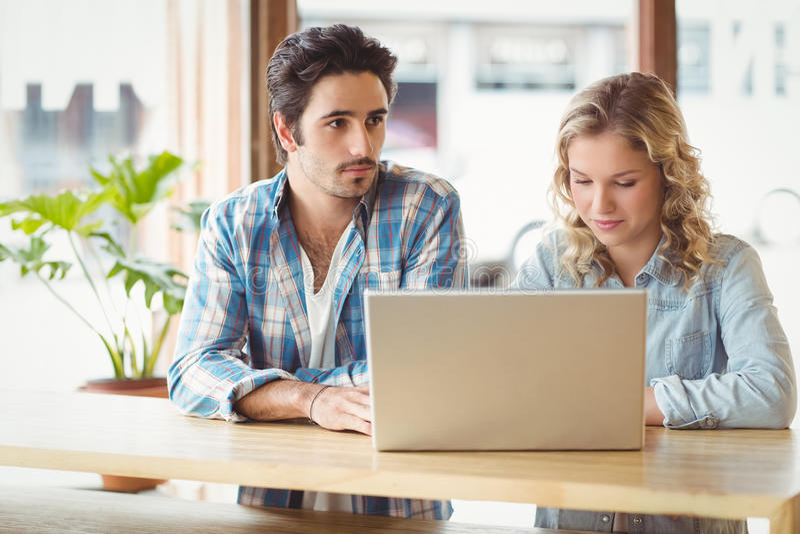 Mann und Frau mit dem Laptop, der im Büro sitzt stockfotografie