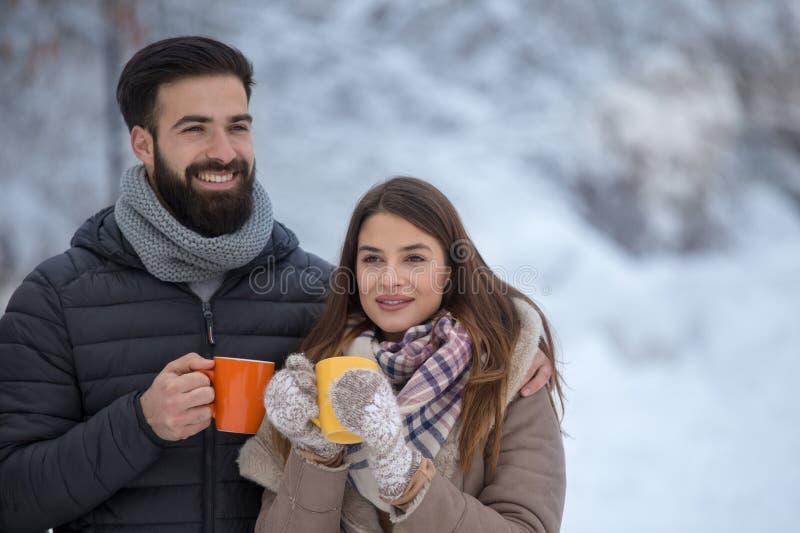 Mann und Frau mit heißem Getränk auf Schnee lizenzfreie stockfotos