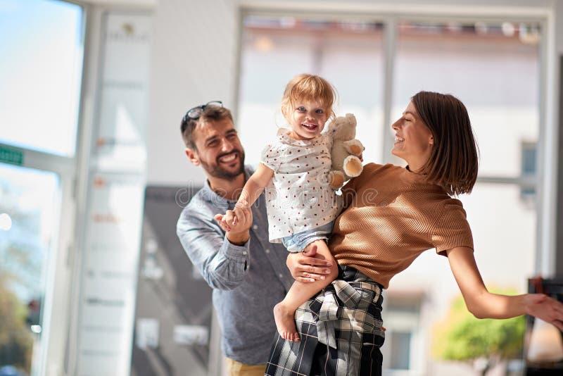 Mann und Frau mit lächelndem Kindermädchen im Speichereinkaufen stockfoto