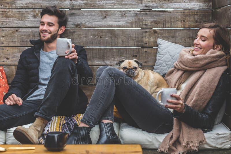 Mann und Frau mit Pug heiße Getränke genießend