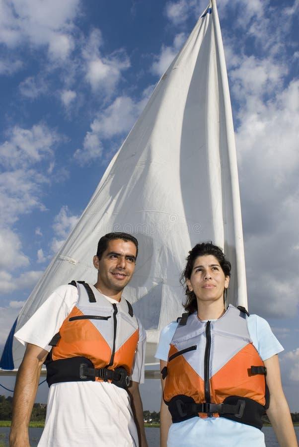 Mann und Frau nahe bei Segelboot auf Wasser - Vertikale stockfotos