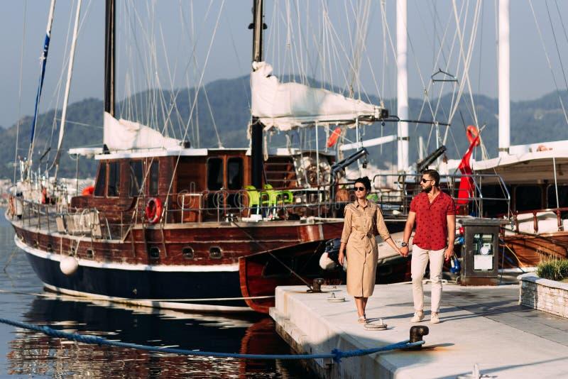 Mann und Frau nahe den Yachten auf dem Dock lizenzfreie stockbilder