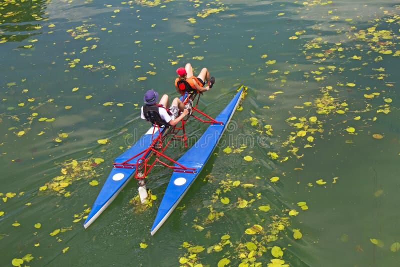 Mann und Frau reiten mit sich hin- und herbewegenden Pedalfahrradbooten stockfotos