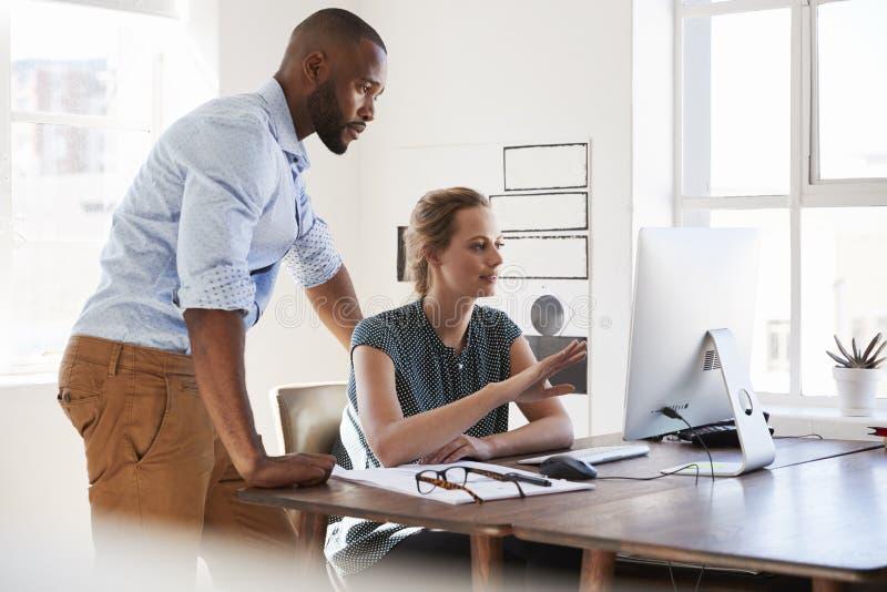 Mann und Frau sprechen in einem Büro, das Bildschirm betrachtet stockfoto