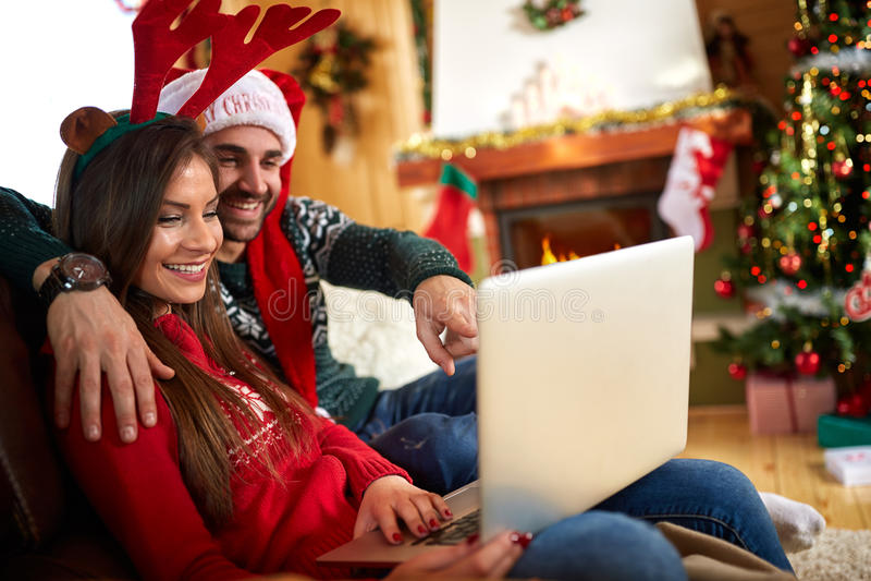 Mann und Frau am Weihnachtsfeiertag mit Laptop lizenzfreie stockfotografie