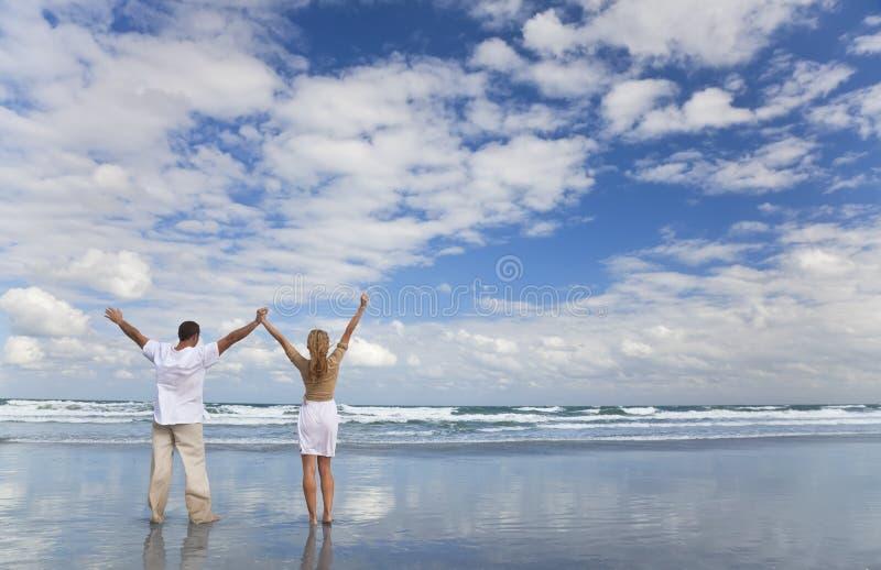 Mann und Frau, welche die Arme angehoben auf einen Strand feiert stockfoto
