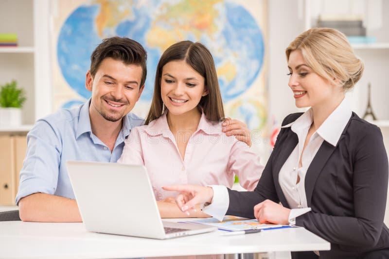 Mann und Frauen im Büro entscheiden sich zu reisen lizenzfreie stockbilder