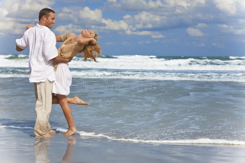 Mann-und Frauen-Paare, die Spaß-Tanzen auf einem Strand haben stockfotografie