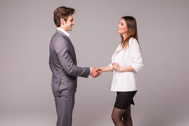 Mann- und Frauengeschäftshändedruck lokalisiert auf grauem Hintergrund Geschäftsmann und Geschäftsfrauhändedruck stockfoto