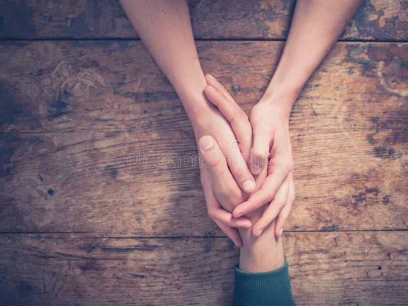 Mann- und Frauenhändchenhalten an einem Tisch stockbild