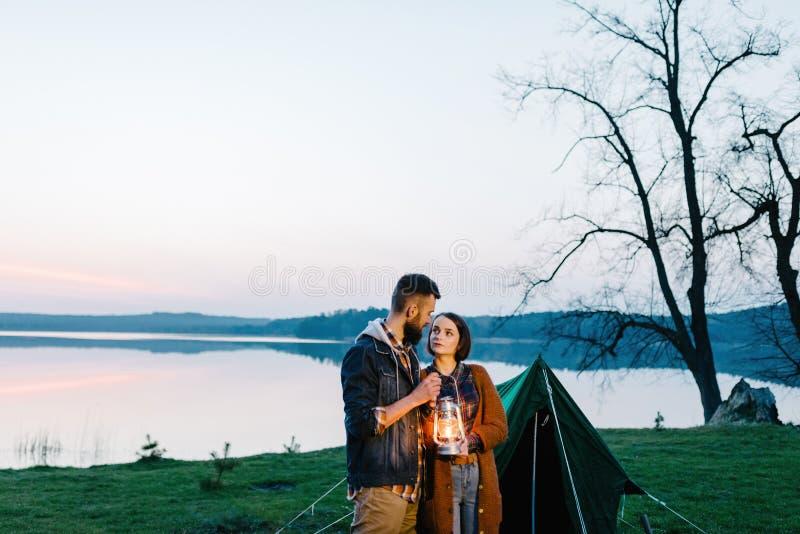 Mann- und Frauenliebhaber halten eine Taschenlampe an der Dämmerung nahe dem See lizenzfreie stockfotos