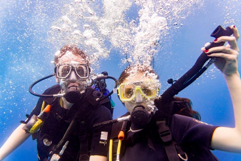 Mann- und Frauensporttaucher im tropischen Meer, das oben taucht lizenzfreies stockfoto