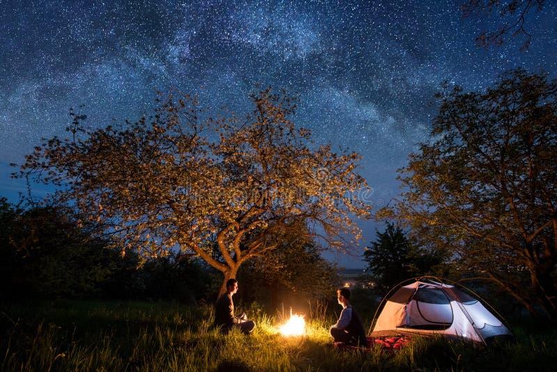 Mann- und Frauentouristen, die voll an einem Lagerfeuer nahe Zelt unter Bäumen und schönem nächtlichem Himmel von Sternen und von stockbild