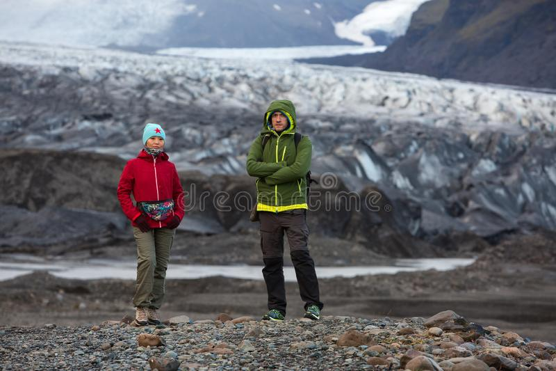 Mann- und Frauentouristen stehen auf dem Hintergrund eines Gletschers in Island lizenzfreie stockfotografie