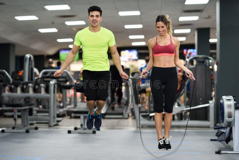 Mann- und Frauentraining mit dem Springen fangen crossfit Turnhalle ein stockfotos
