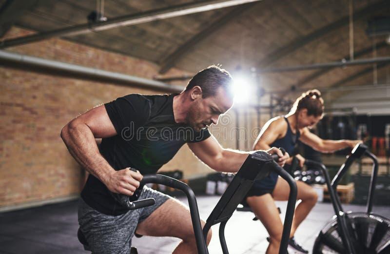 Mann- und Frauentraining mit Turnhallenausrüstung lizenzfreies stockfoto