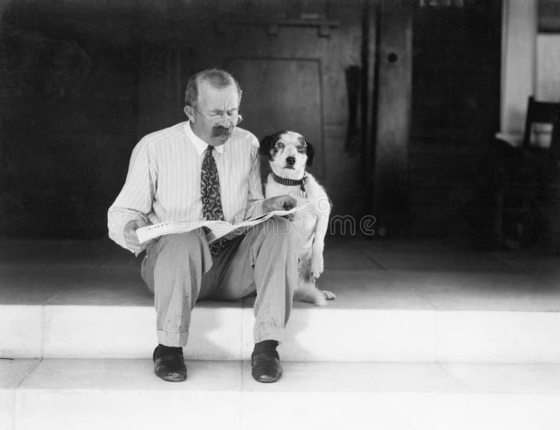 Mann und Hund, die auf den Schritten lesen die Zeitung sitzt (alle dargestellten Personen sind nicht längeres lebendes und kein Z lizenzfreie stockfotografie