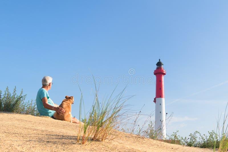 Mann und Hund, die nahe Leuchtturm am Strand sitzen lizenzfreies stockbild