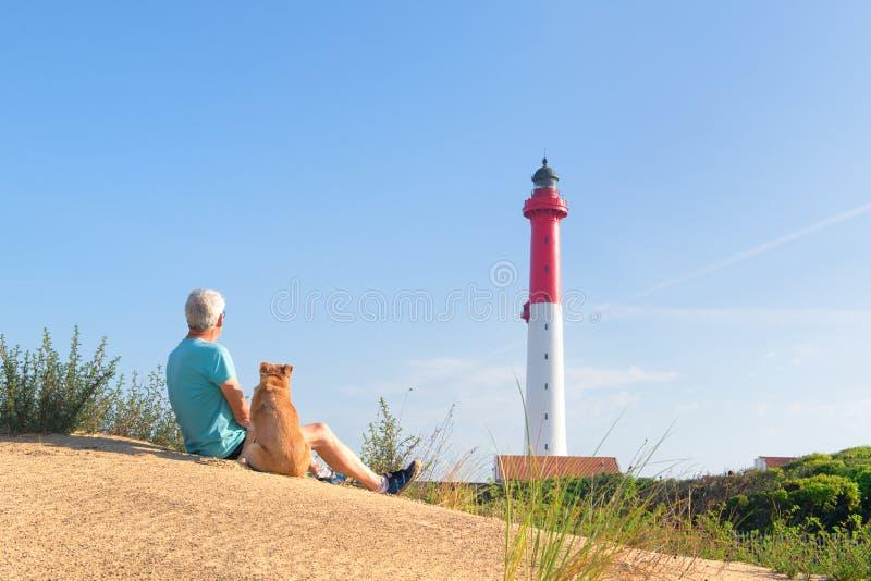 Mann und Hund, die nahe Leuchtturm am Strand sitzen stockfotos