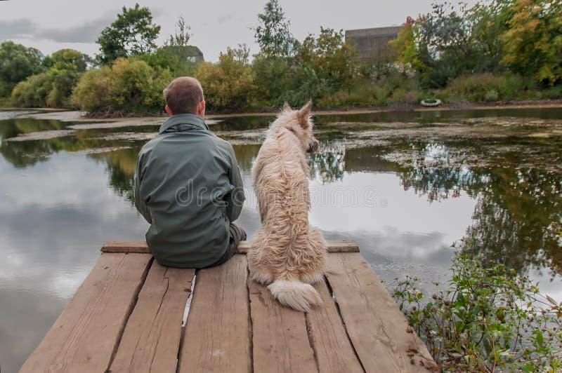 Mann und Hund sitzen auf einem alten hölzernen Pier und einem Blick am See stockfotografie