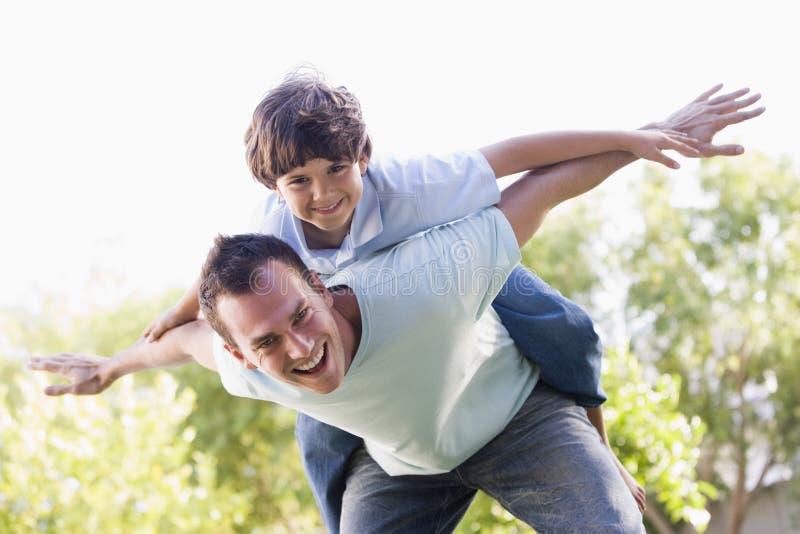 Mann und junger Junge, die draußen Flugzeug spielen lizenzfreies stockfoto