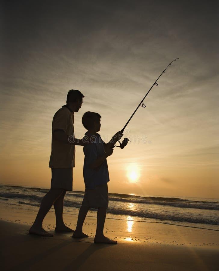 Mann und junges Jungenfischen in der Brandung lizenzfreies stockfoto