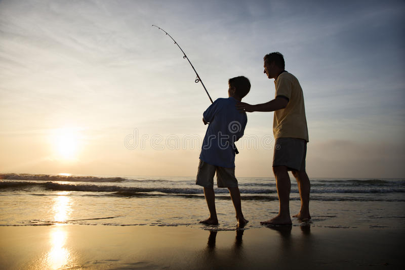 Mann und junges Jungenfischen in der Brandung stockfoto