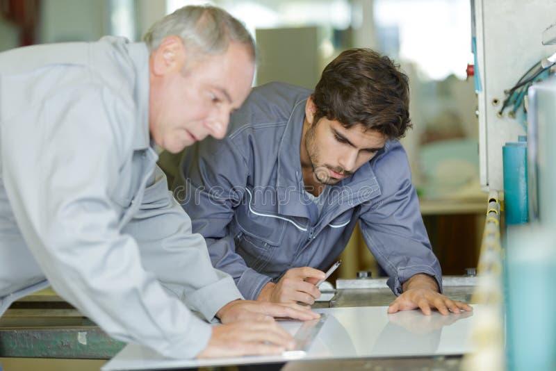 Mann und Lehrling, die an Druckmaschine arbeiten stockbild