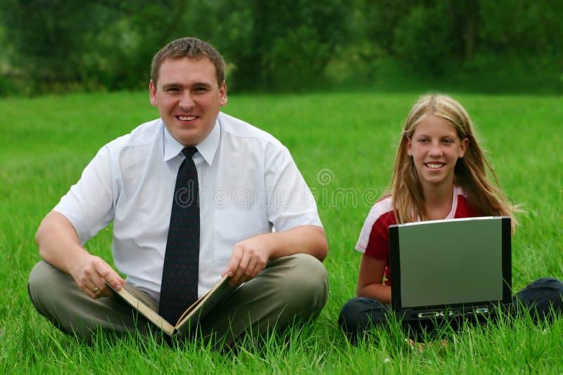 Mann und Mädchen, die auf dem Gras sitzen lizenzfreie stockfotos