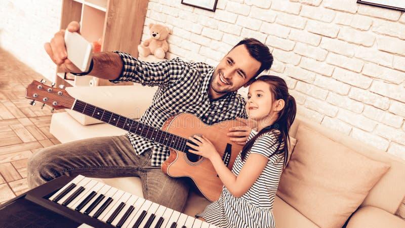 Mann und Mädchen machen Selfie mit Musikinstrumenten lizenzfreies stockfoto