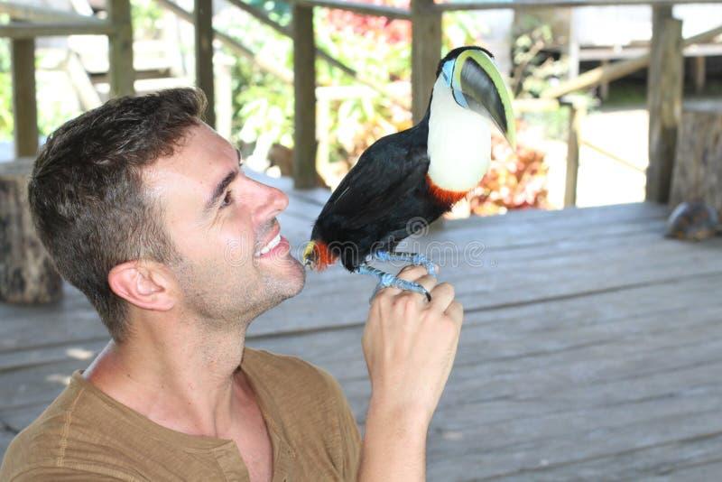Mann und sein domestizierter Tukanvogel stockfoto