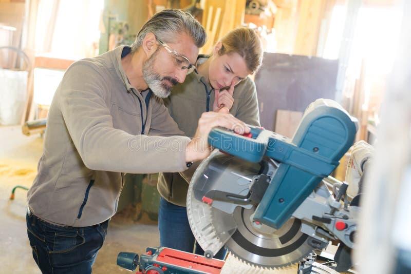 Mann und weiblicher Auszubildender, die hölzerne Planke vorbereitet, wenn Werkstatt gedruckt wird stockfotos