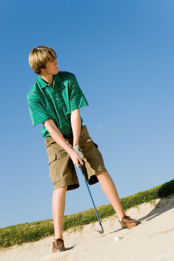 Mann ungefähr, zum des Balls aus einem Sand-Bunker heraus zu schlagen stockbild