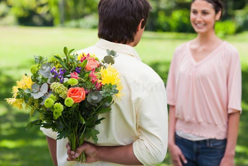 Mann ungefähr, zum eines Blumenstraußes der Blumen darzustellen stockfotos